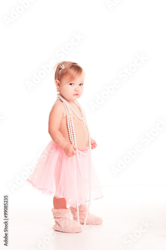 2766e51d7 Smiling baby girl 1-2 year old standing over white. Wearing stylish ...