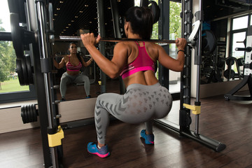 Latino Woman Doing Heavy Weight Exercise For Back