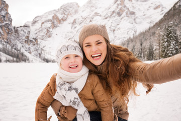 Mother and child taking selfie among snow-capped mountains