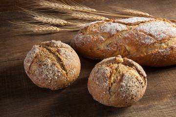 Bread and wheat ears on wooden background