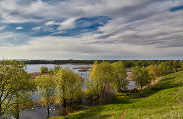 Flood of Volga in the spring, trees and clouds