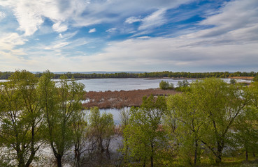 Flood of Volga in the spring, clouds, grass and trees