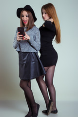 Two cheerful smiling sexy girl girlfriends photographed on the phone, do selfie phone in the studio on a gray background