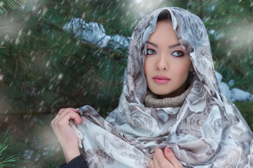 beautiful lovely girl standing under snow in a scarf and warm sweater in the winter forest near the trees