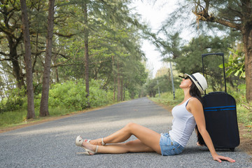 Travel concept. Beautiful woman who waiting cars and relaxing along the road