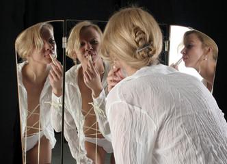 Frau schminkt sich die Lippen vor einem Spiegel