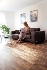 Frau sitzt im Wohnzimmer