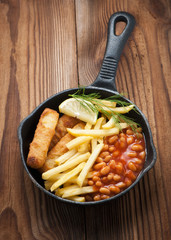 fish fingers, with the meal of baked beans, chips (french fries) and a lemon wedge behind. served on the pan