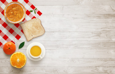 Fruit breakfast with free space for text on wooden table. Jar of jam, juice, tangerine, orange, raspberry, tablecloth, toast, wooden table with top view.