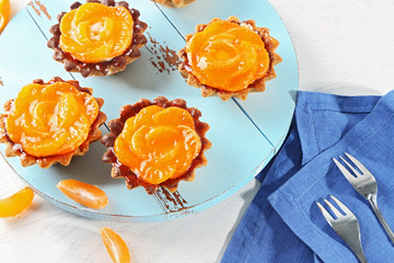 Sweet cakes with tangerines on table, close up