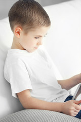 Little boy using tablet on a sofa at home