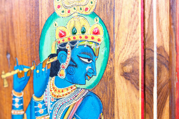 painted blue god. On a wooden background on the market in India