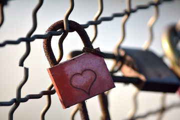Padlock with heart sign hung on the bridge of love
