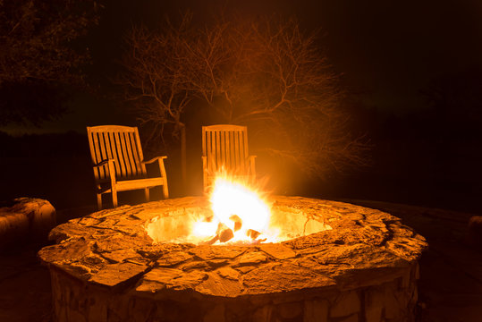 Fire pit aflame with two empty chairs and dark forest