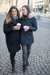 Two women walking in the city with coffee cups