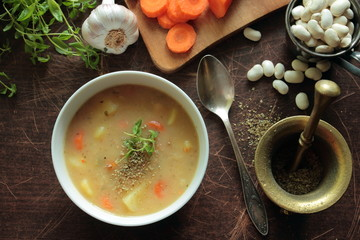 Hot bean soup in a bowl with resh herbs