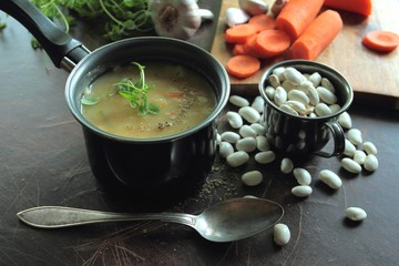 Small pot with bean soup and fresh herbs