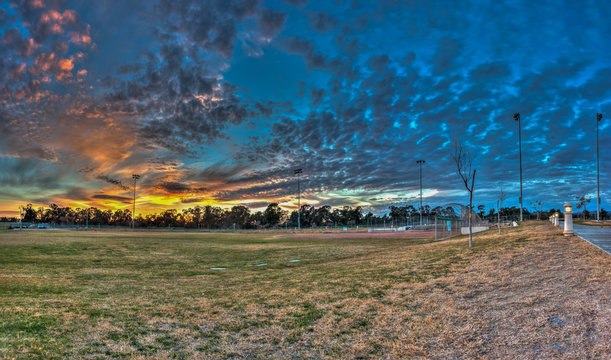 Softball field at sports park under cirrocumulus clouds in panoramic view.