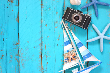 top view image of photo camera, wood boat, sea shells and star fish over wooden table