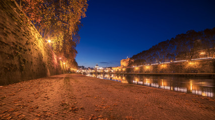 Fototapete - Autumn leaves on embankment of Tiber River in Rome, Italy