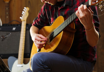 Young man playing acoustic guitar.