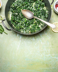 stewed spinach with cream sauce in cooking pot with spoon on rustic background, top view, place for text