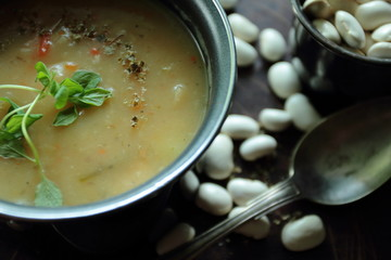 Pot with bean soup with fresh herbs