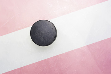 old hockey puck is on the ice with austria flag