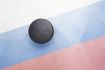 old hockey puck is on the ice with russia flag