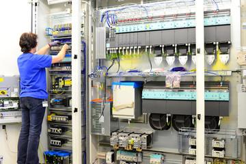 Frau montiert in der industriellen Fertigung von Schaltschränken im Maschinenbau