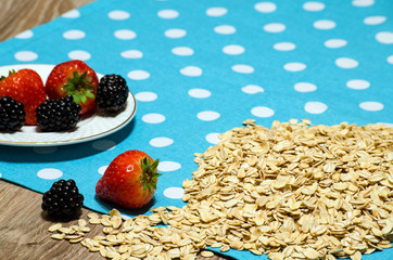 Oatmeal and berries are scattered on the table