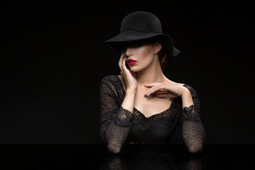 Beautiful girl with red llips in black hat