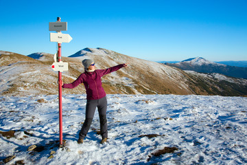 Female Hiker staying at Path Sign and admiring scenic View in Winter Mountains