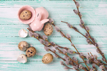 Quail eggs, Easter bunny, willow  branches on wooden background.