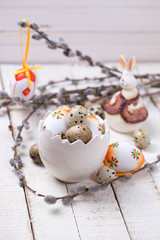 Colorful easter eggs in bowl in form of brocken egg, willow  bra