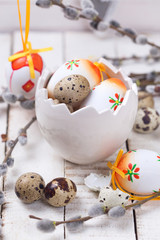 Decorative  easter eggs in bowl  and  willow  branches on wooden