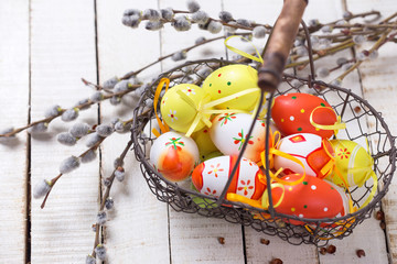 Basket wih easter eggs and willow branches on wooden background.