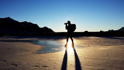 Fotografo su lago ghiacciato al tramonto