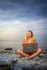 girl laughs looking at a laptop