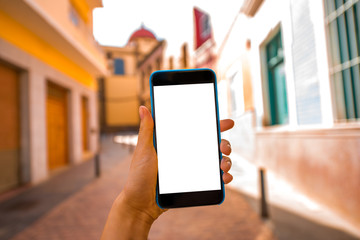 Smartphone with white screen on the old town street background