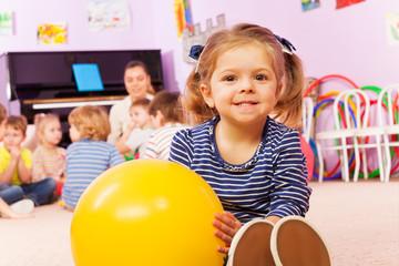 Little girl with ball sit in developmental class