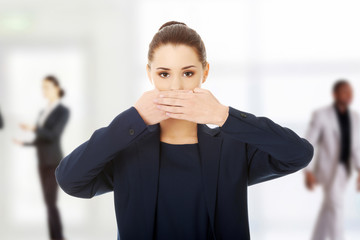 Young businesswoman covering with hand her mouth