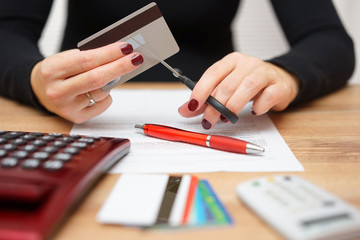 woman is cutting credit card or bank card with scissors over con
