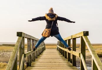 Frau steht auf Holzbrücke