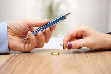 Husband is giving pen to sign divorce papers his former wife aft