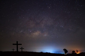Silhouette of cross over milky way
