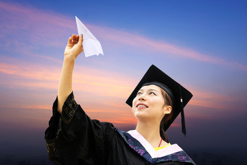 Beautiful female graduate wearing a graduation gown, throwing airplane