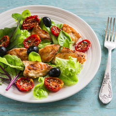 Fresh salad with chicken breast, sun-dried tomatoes, green salad and olives on a white plate on a wooden surface. Healthy food