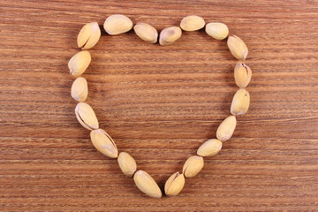 Heart of pistachio nuts on wooden table, healthy eating
