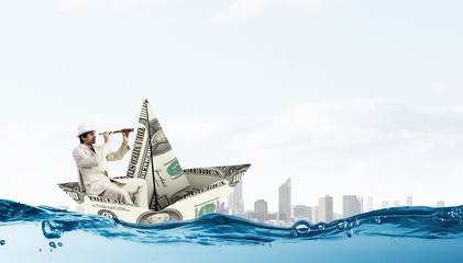 Businessman in boat made of dollar banknote